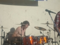 Stephen playing the drums with his old band while pulling a brilliant face